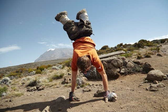 Alex D'Jamoos does a hand stand with Mt. Kilimanjaro in the back